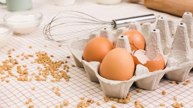 Коричневые яйца в картонной коробке рядом с пшеничным зерном и венчиком над скатертью