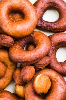 Полный кадр коричневых свежих пончиков на белой поверхности