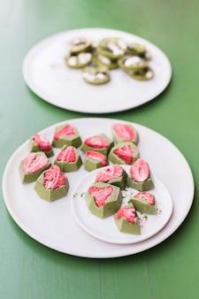 Вкусные десерты с клубникой на белых керамических тарелках на зеленом столе