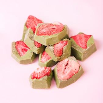 Вкусный десерт с клубникой и зеленым шоколадом на розовом фоне