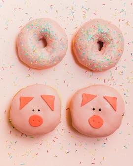 ピンクの壁紙に配置されたおいしい新鮮な装飾ドーナツ