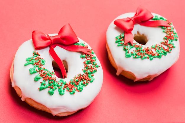 Два украшенные пончики расположены на красном фоне