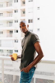 黄色のコーヒーカップを手で押し、バルコニーに立っているアフロの若い男の肖像