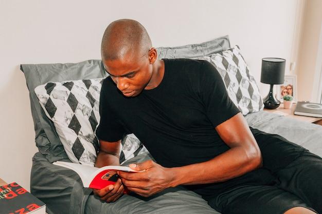 本を読んでベッドに横になっている若いアフリカ人のクローズアップ