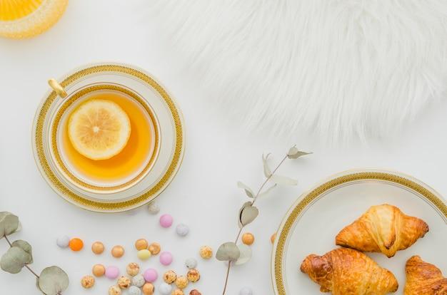 毛皮;焼きたてのクロワッサン。キャンディーと白い背景の上のジンジャーレモンティーカップ