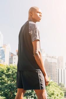 市内の建物に対して立っている運動選手筋肉男の背面図