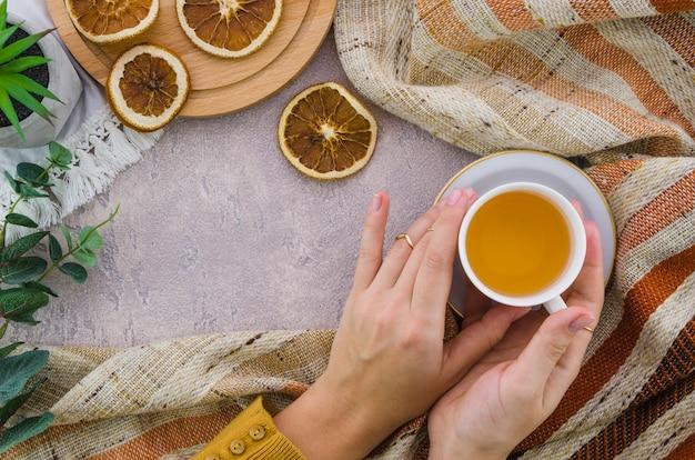 ハーブティーカップと乾燥レモンティーを持っている女性の手のクローズアップ