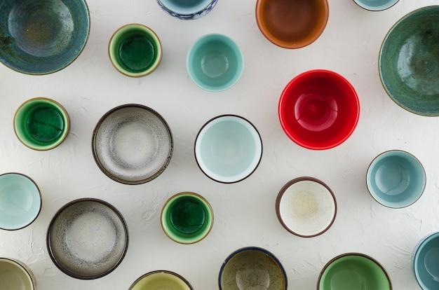 さまざまな種類のセラミックカップと白い背景で隔離のグラス