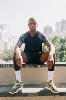 街のスカイラインに対して屋上に座っている自信を持って若い男の肖像