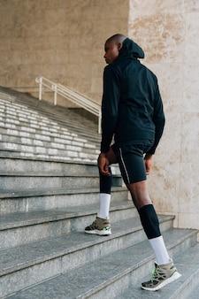 階段の上を歩くパーカートップの男性ランナー