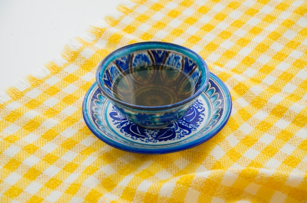 中国の陶器のティーカップと黄色の市松模様のテーブルクロスの上の受け皿