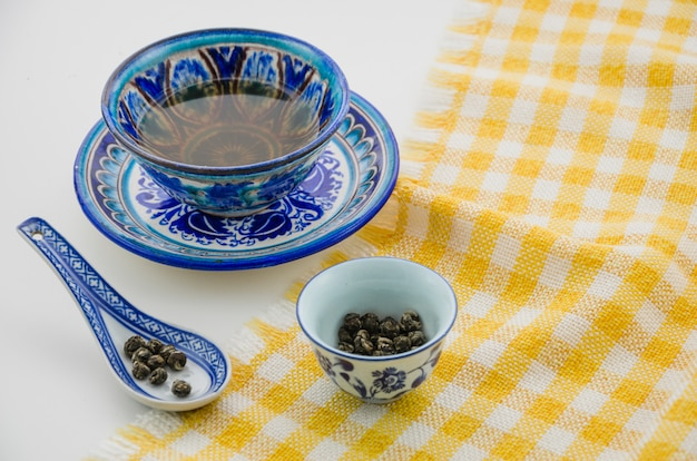 白い背景のテーブルクロスの上のスプーンでウーロン茶ティーカップのクローズアップ