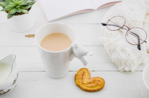 木製の机の上の磁器ホワイトティーカップとパルミエや象の耳のパフペストリークッキー