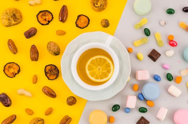 ドライフルーツとキャンディー黄色と白の二重の背景にレモンティーカップ