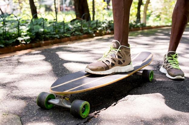 公園でスニーカーで若いスケートボーダーの足をクローズアップ