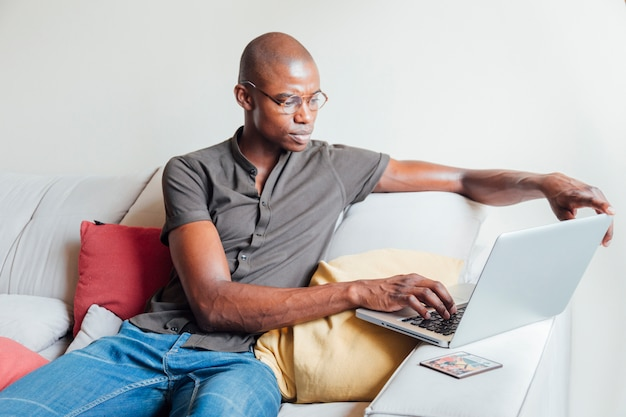 Серьезный африканский молодой человек, сидя на диване, используя ноутбук дома