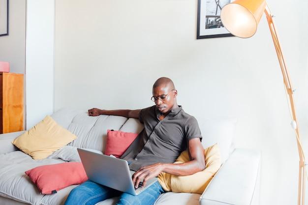 Африканский молодой человек, расслабляющий на диване, используя ноутбук дома