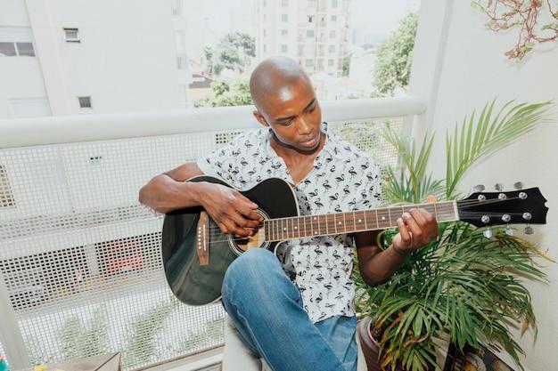 アフリカの若い男がバルコニーに座ってギターを弾く