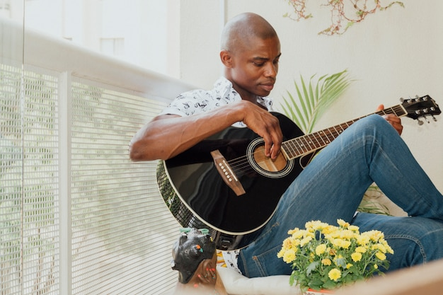 バルコニーでギターを弾くアフリカの若い男のクローズアップ