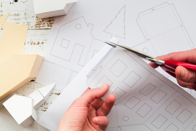 Крупный план руки человека, режущего белую бумагу ножницами