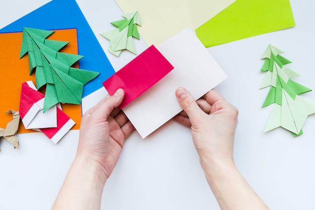 白い背景の上の紙で工芸品を作る人の手の上から見た図