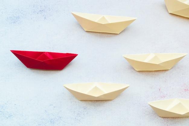 Красный лидер бумажный кораблик лидирует среди белых на текстурированном фоне