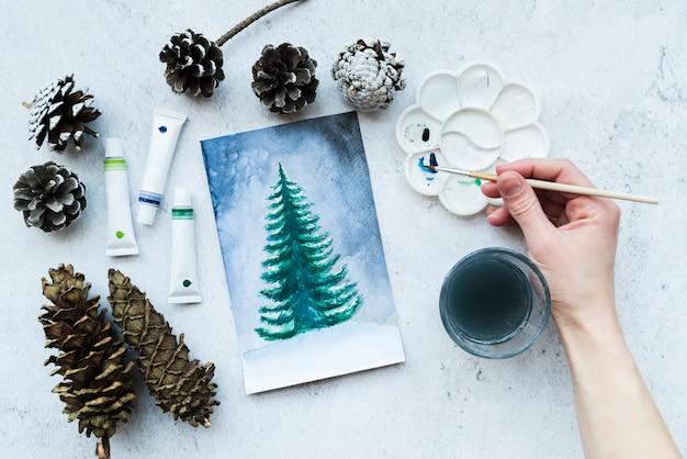 アクリル絵の具の管と人の手の絵画クリスマスツリーのクローズアップ