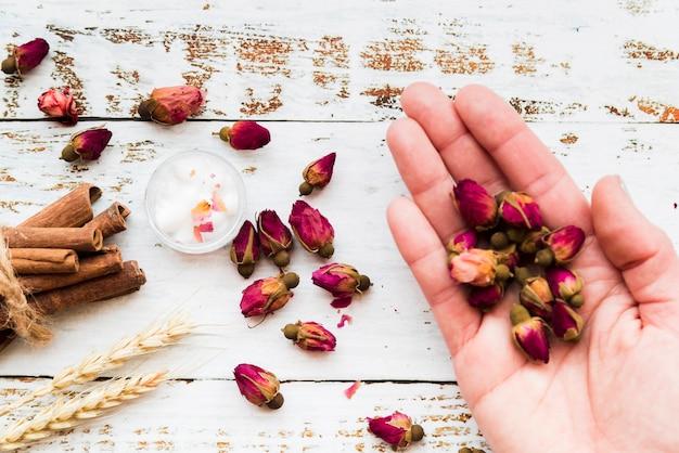 Крупный план сушеных розовых бутонов с корицей; колосья пшеницы и хлопок над деревянным столом