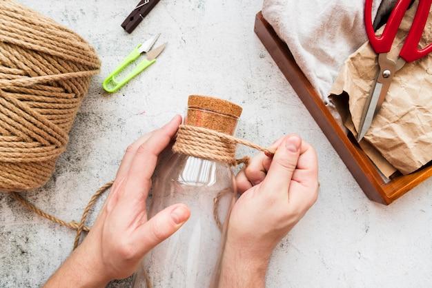 白い織り目加工の背景にガラス瓶の上のジュートのひもを包む人のクローズアップ