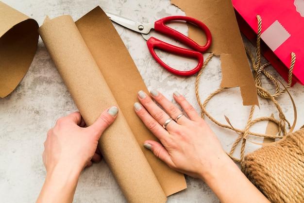 織り目加工の背景に茶色の紙で工芸品を作る女性の手