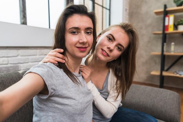 Портрет улыбающиеся лесбиянки молодая пара, сидя на диване, принимая селфи