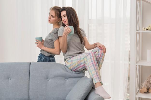 灰色のソファーの近くに手で一杯のコーヒーを保持している若いレズビアンカップル