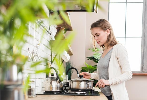若い女性が台所で食べ物を準備します。