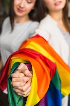 カラフルなレインボーフラグに包まれた若いレズビアンの女性の手のクローズアップ