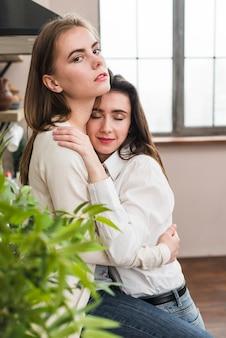カメラを見て彼女のガールフレンドを抱きしめるレズビアンの女性の肖像画