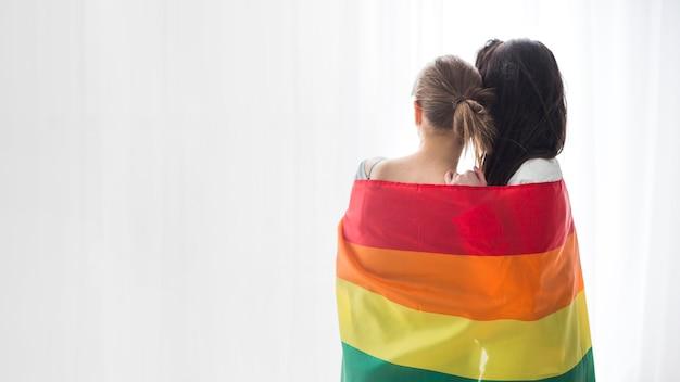 カーテンを見て虹色の旗に包まれた若いレズビアンカップルの背面図