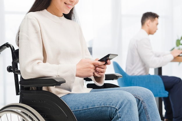 Крупный план улыбающейся неработающей молодой женщины, сидящей на инвалидной коляске с помощью мобильного телефона перед своим коллегой-мужчиной