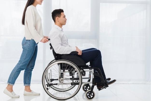 車椅子に座っている若い男を押す女性の笑みを浮かべてください。