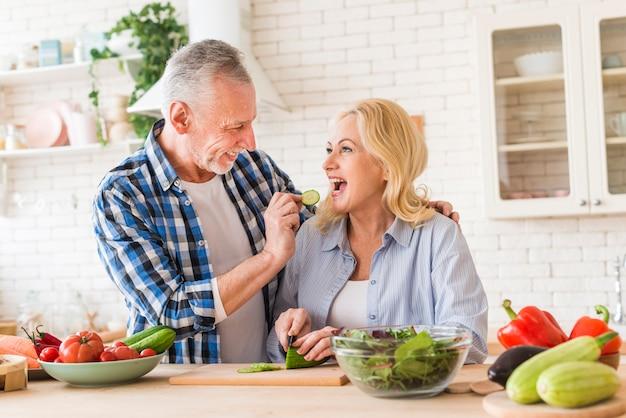 Пожилой мужчина кормит кусочек огурца своей жене на кухне