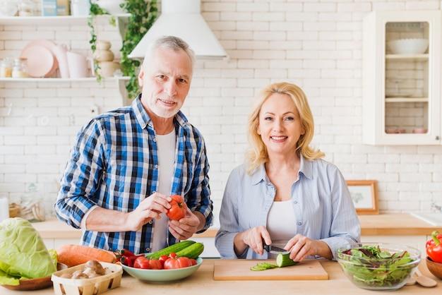 モダンなキッチンでカメラを見て食べ物を準備する年配のカップルの肖像画