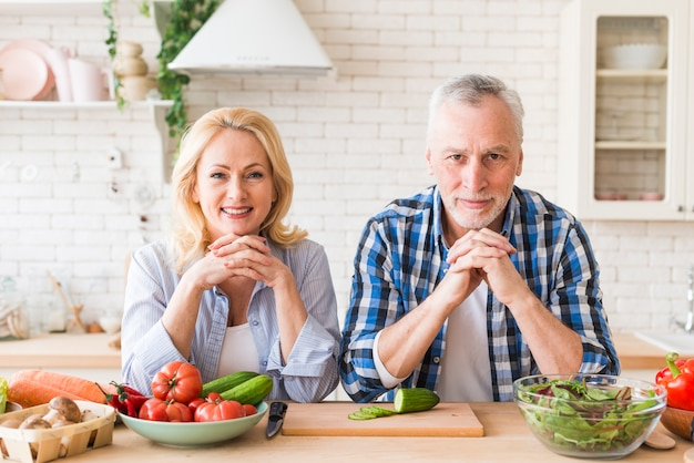 カメラ目線の木製のテーブルにもたれて年配のカップルの肖像画
