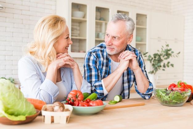 台所でお互いを見ている木製のテーブルにもたれて年配のカップルの肖像画