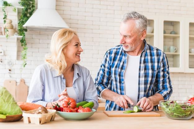 年配の女性が彼女の夫を見てナイフでキュウリのスライスを切る