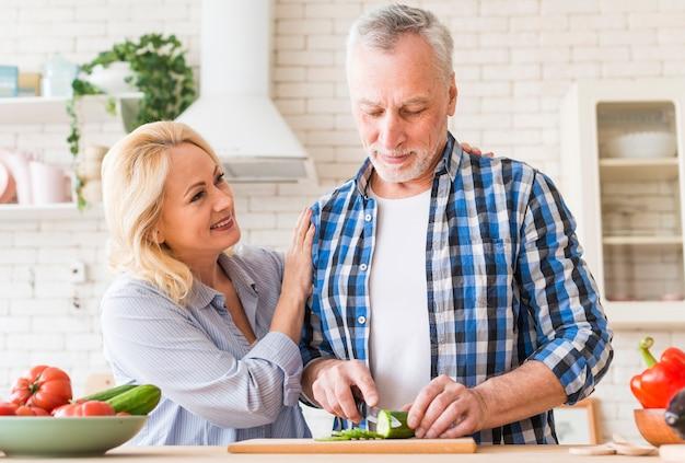台所のテーブルにナイフでキュウリを切る彼女の夫を支える女性の笑みを浮かべてください。