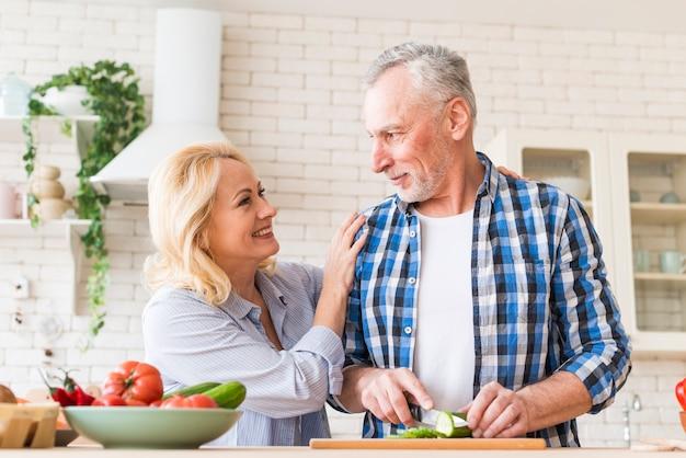 台所で食べ物を準備する年配のカップルの幸せな肖像画
