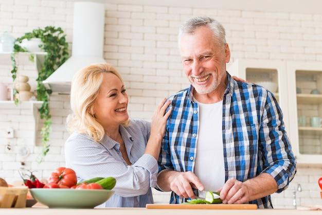台所で食べ物を準備する年配のカップルの笑顔の肖像画