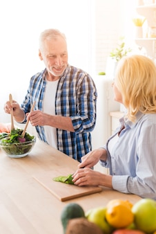 Женщина смотрит на мужа готовит салат на кухне