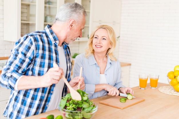 年配のカップル、お互いを見て台所で食べ物を準備します。
