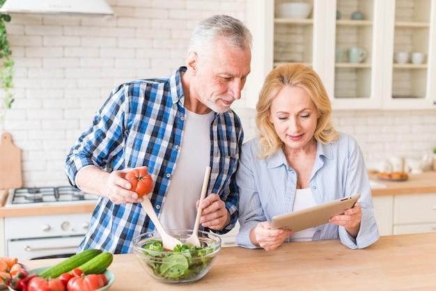 年配の女性が台所でサラダを準備する彼女の夫にレシピを示す