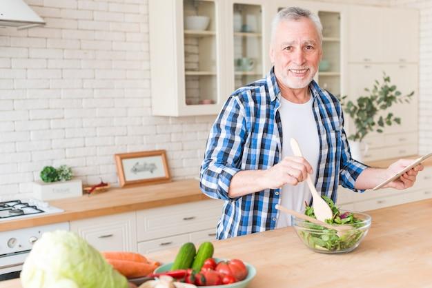 サラダを準備するデジタルタブレットを手で押し笑顔の年配の男性の肖像画